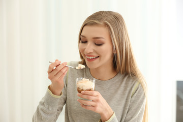 Beautiful young woman with ice cream dessert on light background