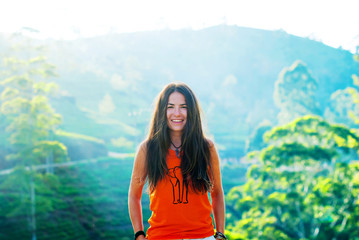 Beautiful girl without makeup with long hair smiles against the background of mountains