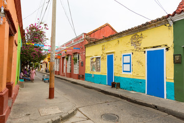 CARTAGENA, COLOMBIA - MAY 24: Unidentified people walk past brightly painted colonial era houses in the Getsemani neighborhood of Cartagena, Colombia on May 24, 2016.