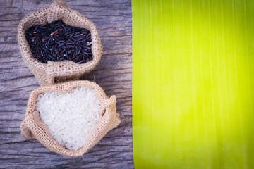 Black rice and Raw grain white rice in burlap bag on wood background,Jasmine rice,