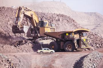 Big shovel loading of copper ore near to pickup truck