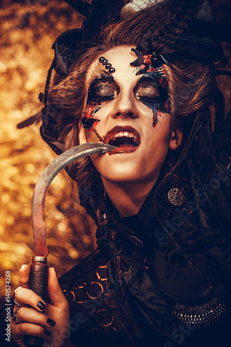 Young witch hloding sickle  Bright make up, skull, smoke
