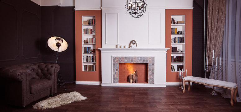 Luxury interior of home library with brown leather sofa, bookshelves, modern fireplace and art lamp tripod. Sitting room with elegant furniture. Wide angle