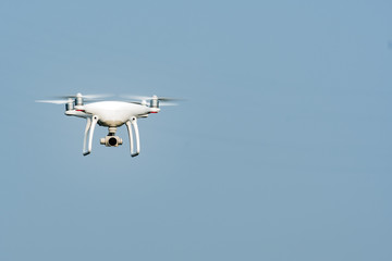 White drone, quadrocopter, with photo camera flying in the blue sky. Drone fly in the blue sky