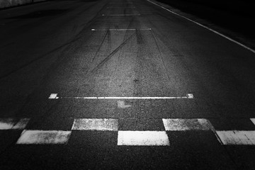 Stores à enrouleur F1 Start and Finish, Front line of asphalt street with sign of start and finish line on road, Black abstract texture and background.