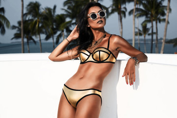Fashion portrait of a beautiful young sexy woman. Dressed in a gold swimsuit with gold accessories, bracelets and necklaces, tanned skin,l body, against a backdrop of palm trees, a photo in a low key