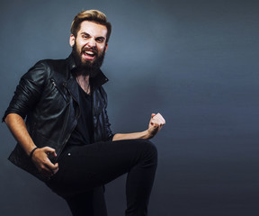 portrait of young bearded hipster guy smiling on gray background close up, brutal man, lifestyle real people concept copyspace