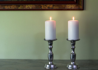 Two lit white candles in canelabra against green wall texture background