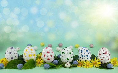 Row of painted speckled chocolate Easter eggs isolated on green background with leaves and flowers