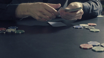 Poker game. Man's hands dealing cards and chips