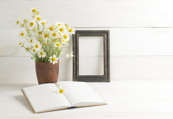 Daisy bouquet  with  photo frame and open notebook