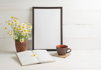 Daisy bouquet  with  motivational frame and open notebook
