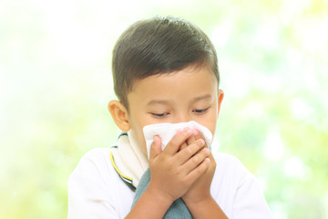 Little boy blowing his nose into tissue. healthcare and medical concept.