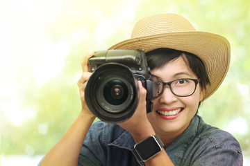 Woman photographer takes images with dslr camera.