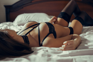 Close-up portrait of a girl in black sexy underwear lying on the bed.