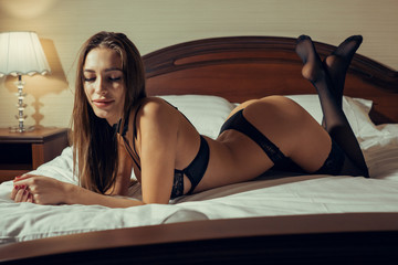 Girl lies on her stomach on a bed in black underwear
