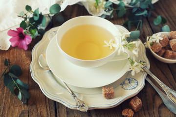 Romantic tea drinking with jasmine tea. Toned image