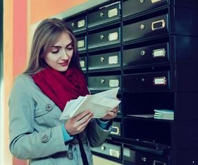 Positive girl in outwear receiving correspondence