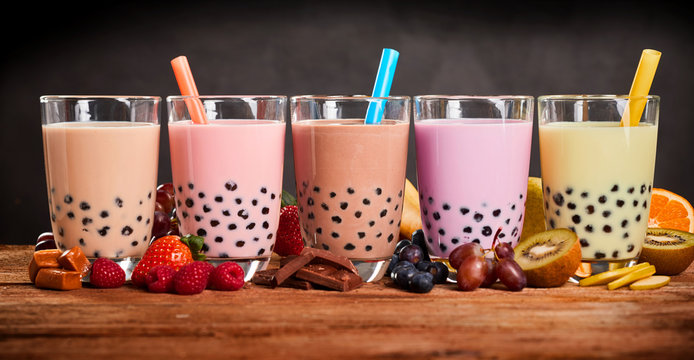 Row of fresh boba bubble tea glasses on wooden background