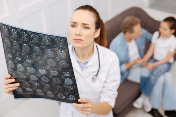 Concerned neurosurgeon carefully studying MRI brain scans