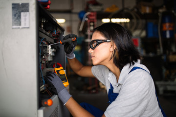 Female mechanic fixing a compressor engine