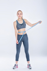 beautiful fitness girl in sportswear measures waist with measuring tape on gray background