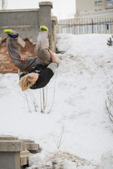 Teenager blonde hair guy training parkour jump flip in the snow covered park