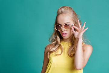 portrait of beautiful blond woman in sunglasses and yellow shirt on turquoise background. Carefree summer.