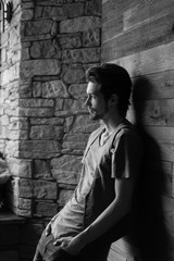 Black and white side view of stylish young man leaning on wall indoor