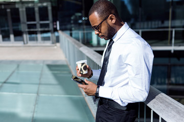 Young male with coffee and phone