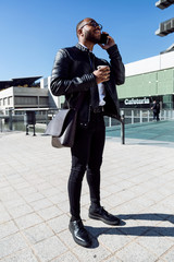 Young content using a phone and holding a coffee mug