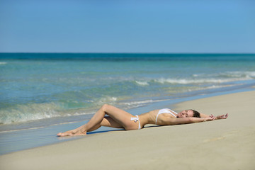 Beautiful young blond woman in white swimsuit is lying on the sand of caribbean beach near azure sea