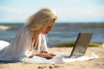 Smiling beautiful young woman at the seaside using a laptop