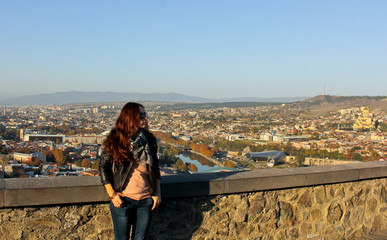 Girl in the sunglass looks. Panoramic view of old Tbilisi, Georgia at the background. Traveler woman walking around the city by looking at the view from above. The view from the castle Narikala.
