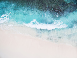 Beautiful tropical white empty beach and sea waves seen from above. Seychelles Grand Anse beach aerial view