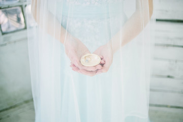 Seashell in the hands of the bride