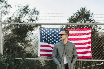 Man wearing sunglasses standing at the chain wire wall with the USA flag. Horizontal outdoors shot.