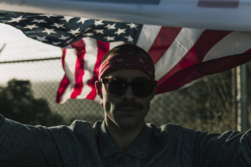 Man with USA�flag over head