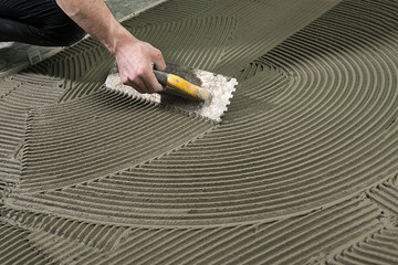 Worker Applying Ceramic Glue