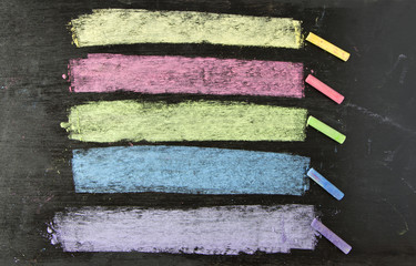 colorful chalks on blackboard background.