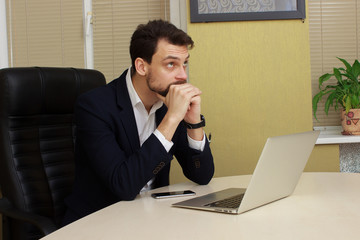 businessman sitting at desk on laptop