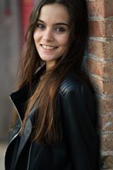 Cheerful woman at brick wall