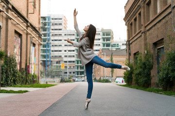 Horizontal outdoors shot of a woman in the street performing a ballet.
