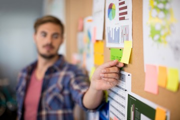 Man touching sticky note on the board