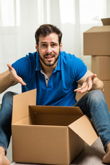 man lying on the floor with packing boxes behind