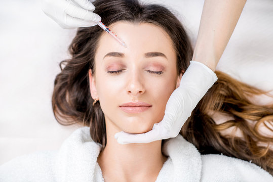 Woman receiving cosmetic injection in forehead