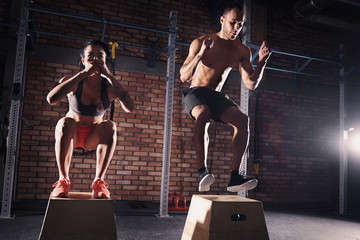 Fitness couple jumping on platforms in gym