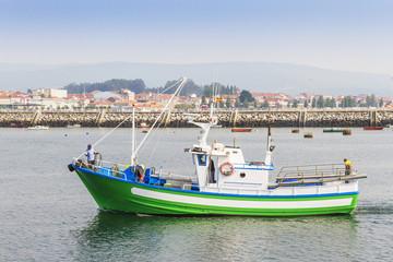 Green fishing boat at harbor