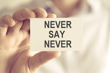 Businessman holding NEVER SAY NEVER message card