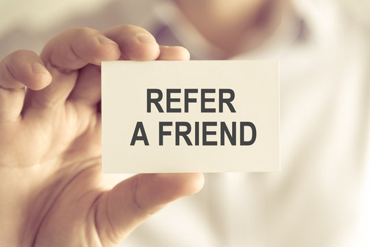 Businessman holding REFER A FRIEND message card